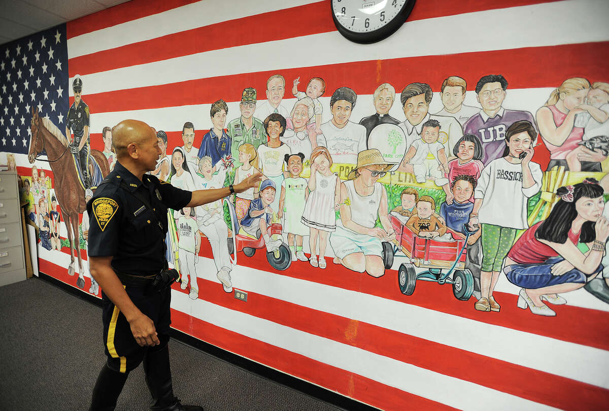 Bridgeport Mounted Police Officer Tom Choothesa discusses his wall-sized mural, featuring 70 portraits representing the range of residents in the Bridgeport community, in the chief's office at Bridgeport Police Headquarters in Bridgeport, Conn. on Wednesday, September 9, 2015. Painted in 2001, the mural took Choothesa about 200 hours to complete.