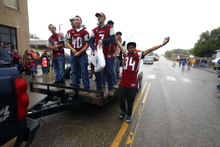 Jayy Morgan (right) and his fellow high school football players ride in a parade in Alexander, N.D., part of the town's annual Old Settlers' Day celebrations. Photo: Martha Irvine, Associated Press