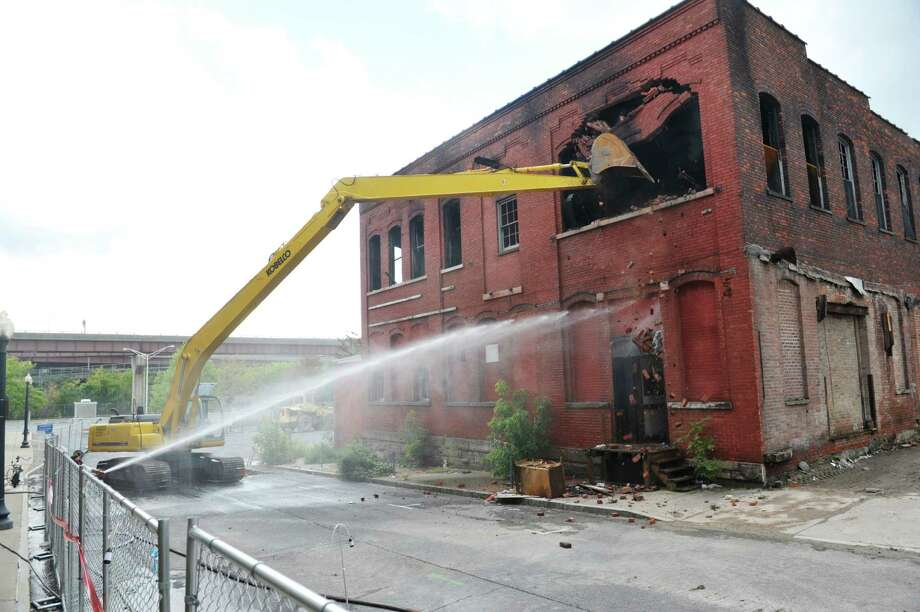 Demolition crews work on knocking down the building at 32 Spencer St. on Sunday, Sept. 13, 2015, in Albany, N.Y.  The building was damaged by fire on Saturday.  (Paul Buckowski / Times Union) Photo: PAUL BUCKOWSKI / 00033339A