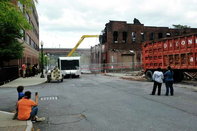 Adults and children watch as a demolition crew works on knocking down the building at 32 Spencer St. on Sunday, Sept. 13, 2015, in Albany, N.Y.  The building was damaged by fire on Saturday.  (Paul Buckowski / Times Union) Photo: PAUL BUCKOWSKI / 00033339A