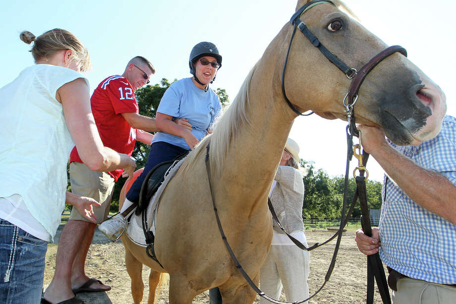 Bruce Jennings (second from left) helps his daughter, Cameron Jennings, 16, mount Schooner in preparation for her Hippotheraphy exhibition ride during EquesFest, a day of family fun activities sponsored by the Saddle Light Center for Therapeutic Horsemanship at Rio Cibolo Ranch in Marion on Sunday, Sept. 13, 2015.  The event featured pony rides, a petting zoo, a hay ride and Mule Team ride, face painting, games, a silent auction, an arena show, music and food.  MARVIN PFEIFFER/ mpfeiffer@express-news.net Photo: Marvin Pfeiffer, Staff / San Antonio Express-News / Express-News 2015