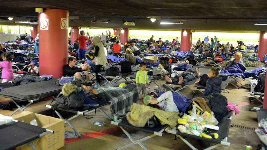 "Refugees rest in a parking garage in the main rail station in Salzburg Austria, Sunday, Sept. 13, 2015. At least four countries Friday firmly rejected a European Union plan to impose refugee quotas to ease a worsening migrant crisis that Germany's foreign minister said was ""probably the biggest challenge"" in the history of the 28-nation bloc. (AP Photo/Kerstin Joensson) ORG XMIT: XKJ106 Photo: Kerstin Joensson / AP"