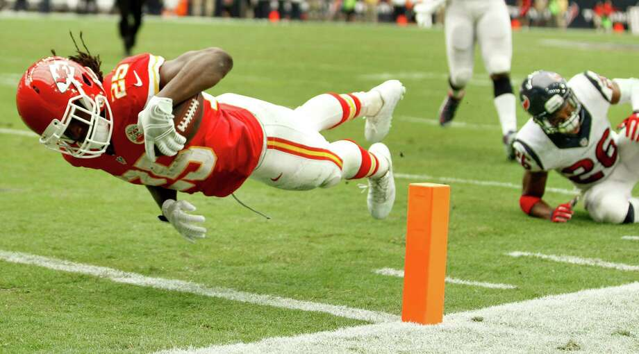 Chiefs running back Jamaal Charles dives into the end zone after beating Texans defensive back Rahim Moore (26) for a 7-yard TD catch. Photo: Brett Coomer, Staff / © 2015  Houston Chronicle