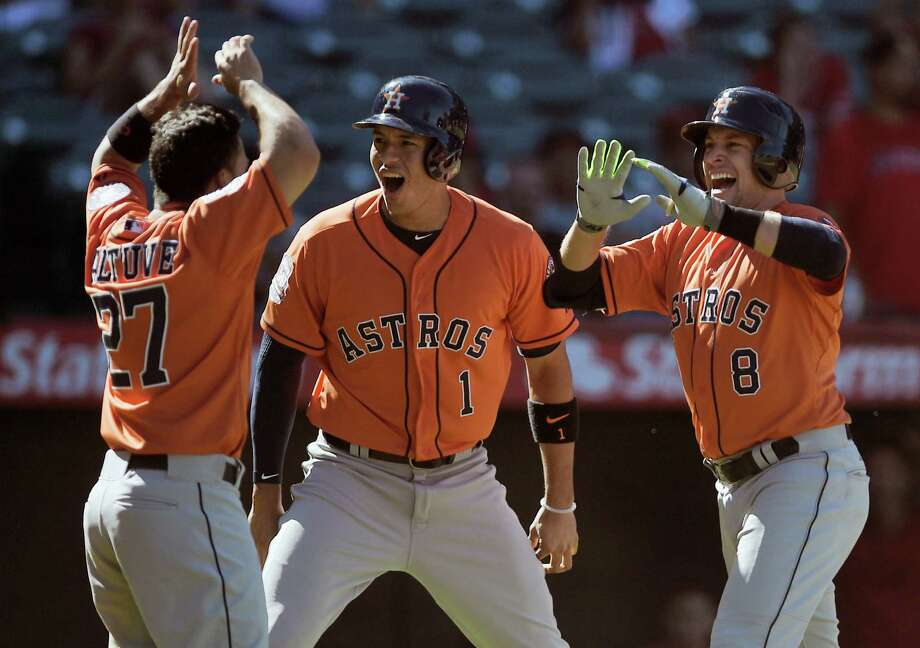 The Astros' Jose Altuve, left, and Carlos Correa, center, celebrate pinch hitter Jed Lowrie's game-winning three-run homer that came with two outs in the ninth inning Sunday against the Angels. Photo: Kelvin Kuo, FRE / FR170752 AP