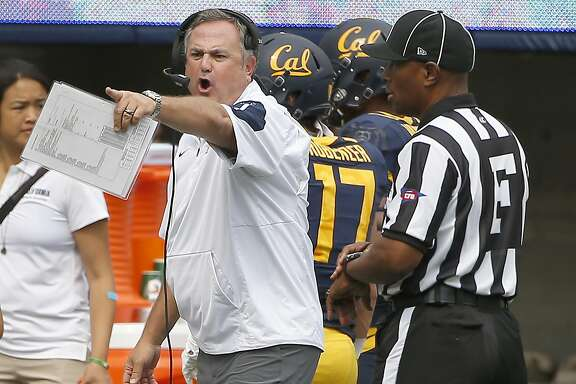 California head coach Sonny Dykes, center, argues a call with the referee during the first half against San Diego State of an NCAA college football game Saturday, Sept. 12, 2015, in Berkeley, Calif. (AP Photo/Tony Avelar)