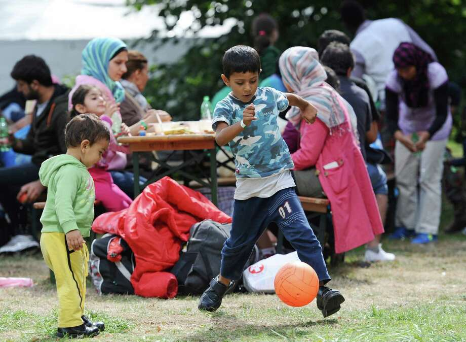 Boys play with a ball  at a tent village for migrants and refugees  at the Donnersberg bridge close to the central train station in Munich, Germany, Sunday Sept. 13,  2015. Hundreds of thousands of Syrian refugees and others are still making their way slowly across Europe, seeking shelter where they can, taking a bus or a train where one is available, walking where it isn't.  (Andreas Gebert/dpa via AP) Photo: Andreas Gebert, AP / dpa