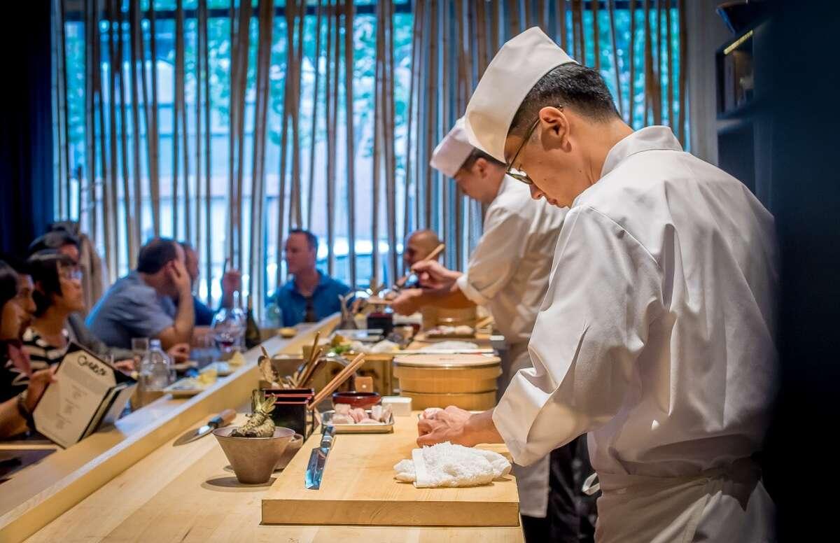 Chefs Ingi Son, front, and Jackson Yu make sushi