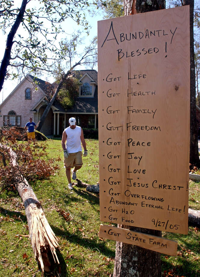 A sign listing blessings hangs in a yard as Greg Owens of McAllen, Texas (left) and Jared Best (right) of Silsbee remove hurricane debris in Silsbee on Monday, October 3, 2005. Hardin County is one of nine Texas counties designated for Hurricane Rita relief.  Beaumont Enterprise Photo: Mark M. Hancock, Staff Photographer / © 2005 The Beaumont Enterprise
