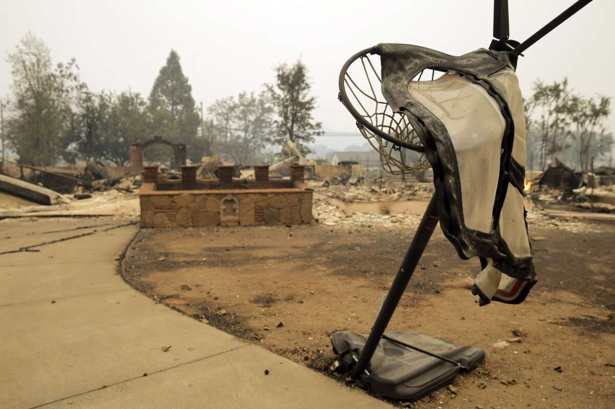 A melted basketball hoop and backboard is all that remains in front of a house in Middletown, Calif., on Sunday, September 13, 2015, the day after a wildfire swept through town destroying homes and forcing mass evuations.