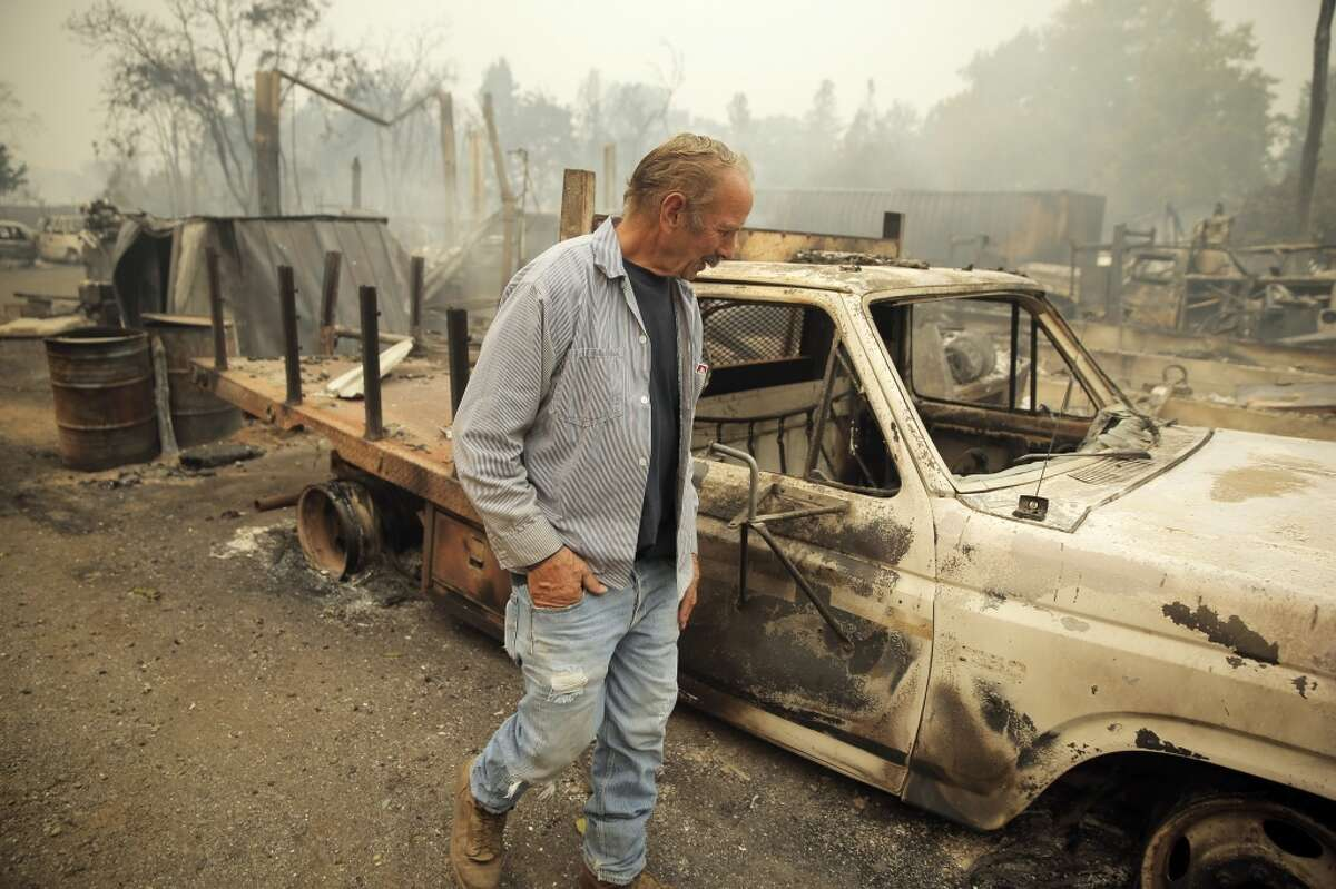 Larry Menzio looks over the remains of his tire shop Menzio Tire in Middletown, Calif., on Sunday, September 13, 2015, the day after a wildfire swept through town destroying hundreds of homes and forcing mass evacuations.