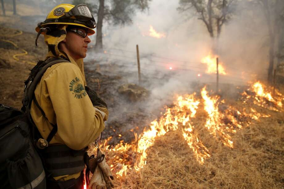 Tyler Fiske talks to another firefighter while using a flare to make a fire line to help contain the Valley Fire near Hidden Valley Lake, California, on Sunday, Sept. 13, 2015. Photo: Connor Radnovich, The Chronicle