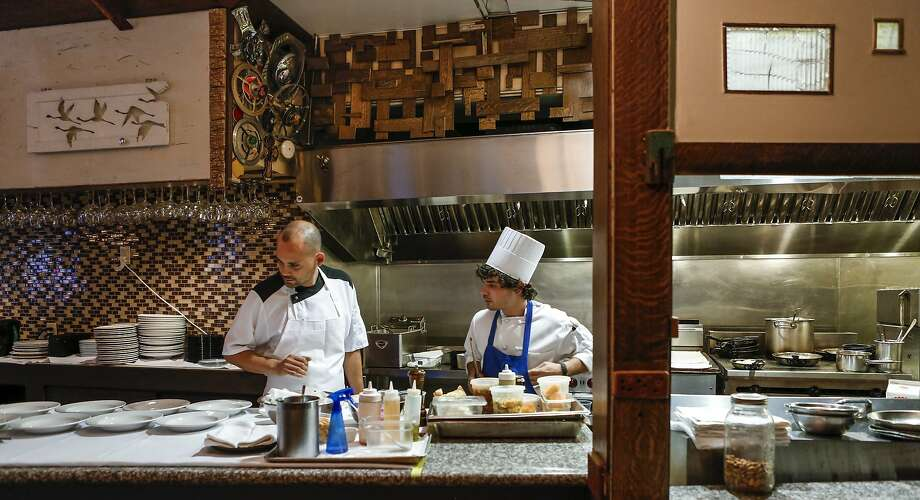 Chef Manny Torres Gimenez (left) discusses orders with sous chef Wesley Rowell at the Palace. Torres and his wife own and run two restaurants in the Mission District. Photo: Russell Yip, The Chronicle