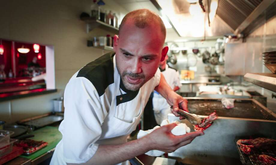 Chef Manny Torres checks an order while cooking at Coco Frio in S.F. Photo: Russell Yip, The Chronicle