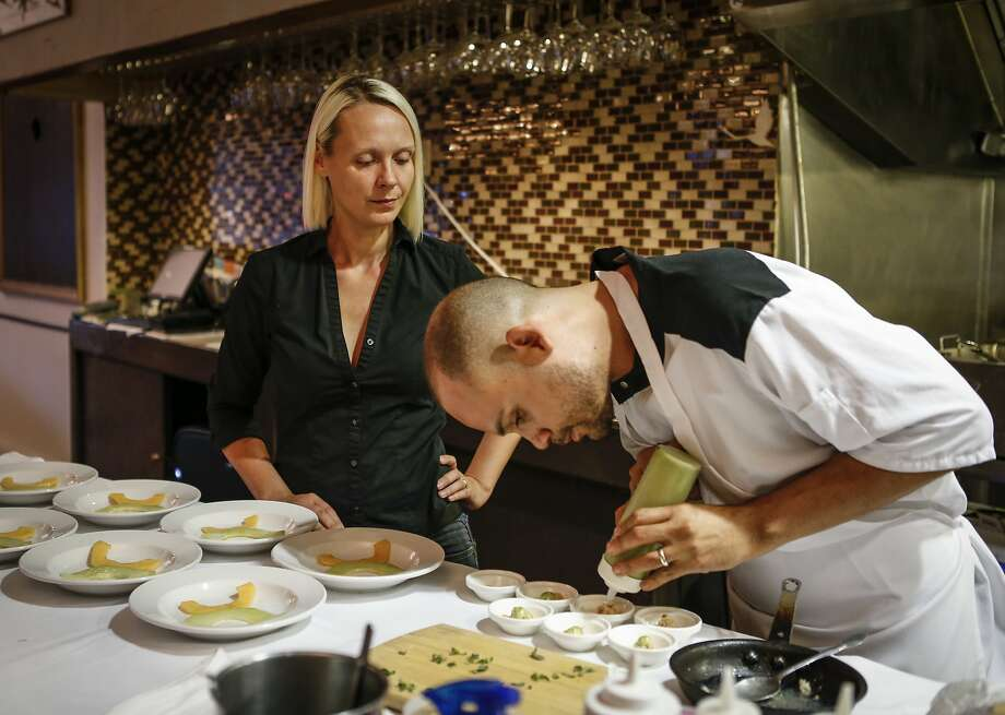 Chef Manny Torres Gimenez plates an order while his wife, Katerina De Torres, waits to deliver them at their sister restaurant, the Palace, in S.F. The couple also own and run new restaurant Coco Frio. Photo: Russell Yip, The Chronicle