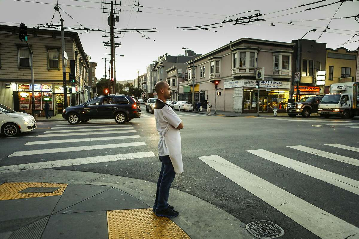 Chef Manny Torres waits for the light as he walks between his two restaurants, Coco Frio and the Palace in S.F. With little staff and without seeking investors, Torres and his wife, Katerina, run the two restaurants, bouncing between them nightly.