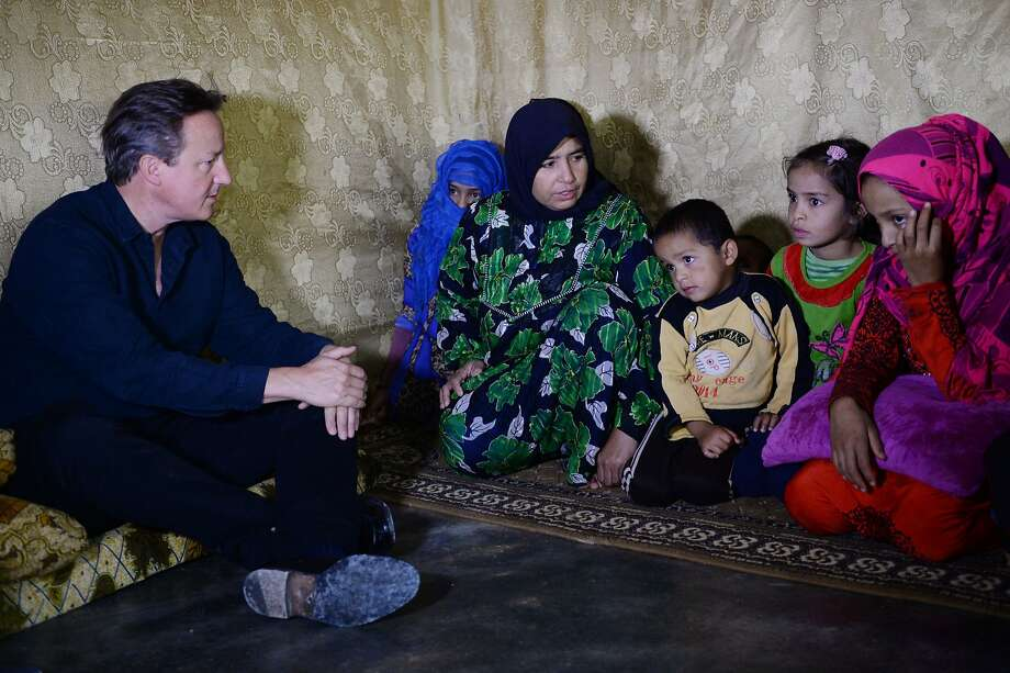 British Prime Minister David Cameron (left) meets Syrian refugee families at a tented settlement camp in the Bekaa Valley on the Lebanese-Syrian border. Cameron arrived in Beirut Monday for a one-day visit to discuss the Syrian refugee crisis gripping the Middle East and Europe, a Lebanese government source said. Cameron was to visit a refugee camp in the Bekaa valley in eastern Lebanon, the source said. The country hosts more than 1.1 million Syrian refugees. Photo: Stefan Rousseau, AFP / Getty Images
