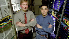 Rackspace.com's Graham Weston (left) and Richard Yoo with some of the hundreds of servers at their office.