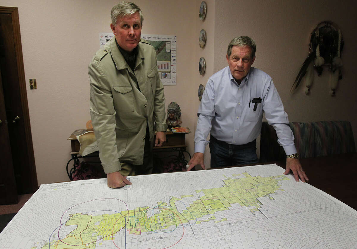 Geologist Gregg Robertson (left) worked with people at Petrohawk Energy in Houston. Their discovery in La Salle County turned out to be the Eagle Ford shale formation. Standing with Robertson is Robert Graham, a landman who helped put together leased acreage on the Eagle Ford area. On the table is a map of the Eagle Ford area.