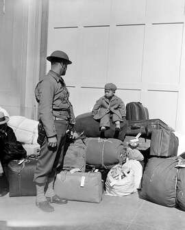 Perched high on a pile of baggage and with a military policeman watching, a little Japanese boy is awaiting the return of his parents, April 6, 1942, in San Francisco, California. More than 650 citizens of Japanese ancestry are evacuated from their homes and sent to Santa Anita racetrack, now an assembly center for war relocation of alien and American-born Japanese civilians. (AP Photo)