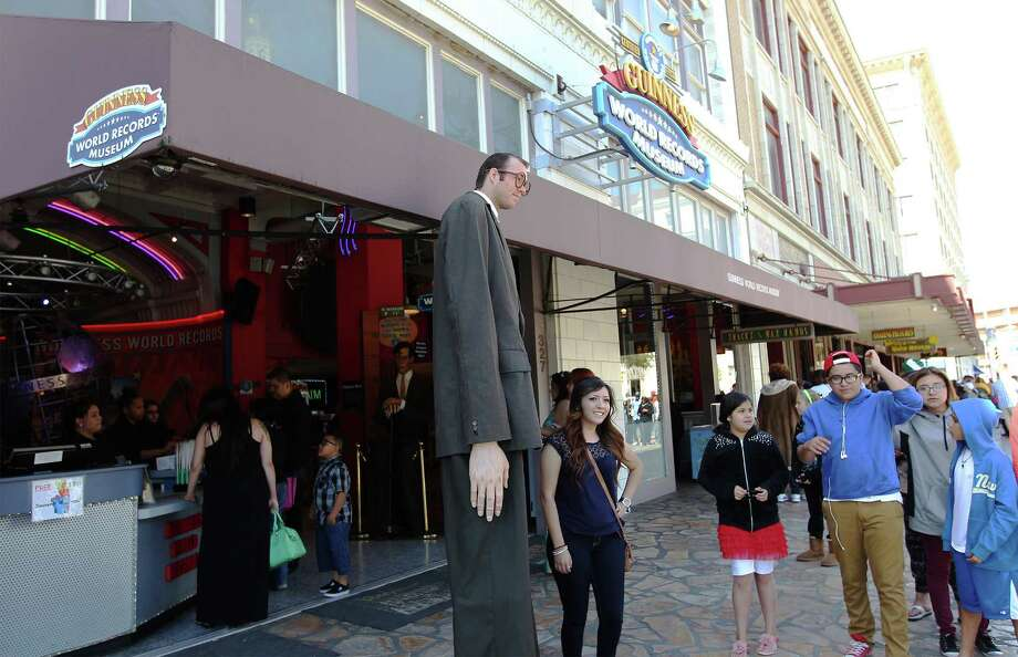 An actor portraying the tallest man takes photos with tourists outside the Guinness World Records Museum along Alamo Plaza in 2014. Photo: Kin Man Hui /San Antonio Express-News / ©2013 San Antonio Express-News