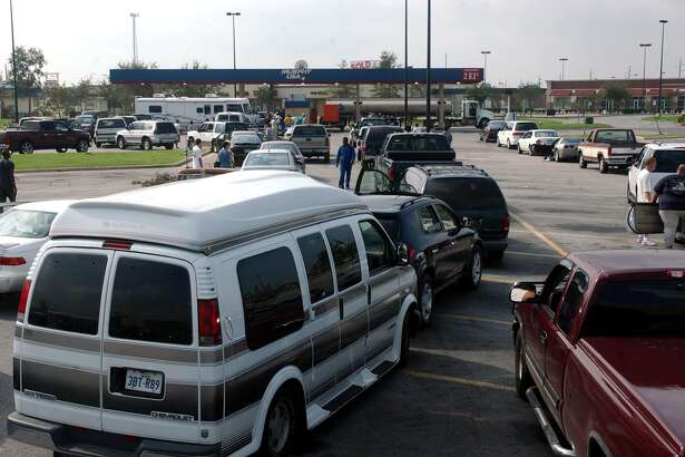 People wait in line to fill up their cars with gasoline at Wal-Mart in Beaumont on Monday, September 26, 2005. Wal-Mart brought a portable generator to power the pumps. (AP Photo/The Beaumont Enterprise, Mark M. Hancock)
