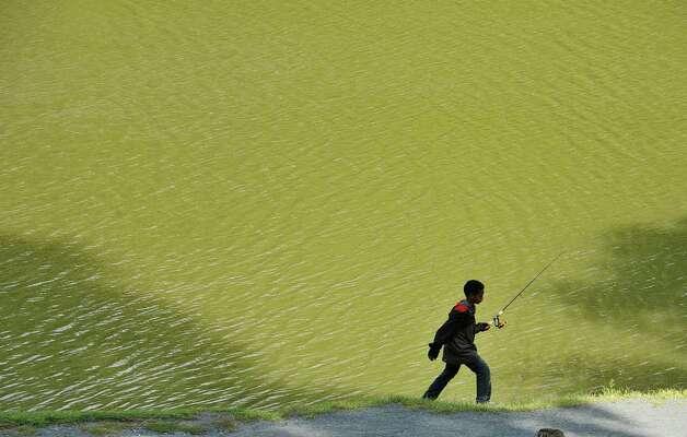 Muath Sidig, 11, of Albany fishes in Washington Park lake on Monday, Sept. 14, 2015, in Albany, N.Y. (Paul Buckowski / Times Union)