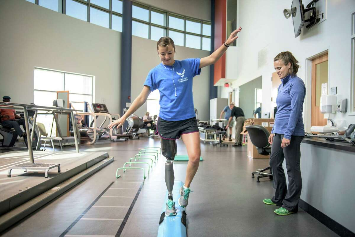 """Christy Wise, 28, a pilot in the Air Force, balances on her prosthesis as physical therapist Alicia White watches at the Center for the Intrepid in San Antonio on July 13. Wise, in the military for 10 years and a helicopter pilot for six, lost her leg above the knee in a boating accident in Florida a few months back. Now she's doing therapy in order to start flying again and to build the non-profit she started, """"One Leg Up On Life Foundation,"""" that provides protheses for children in Haiti."""