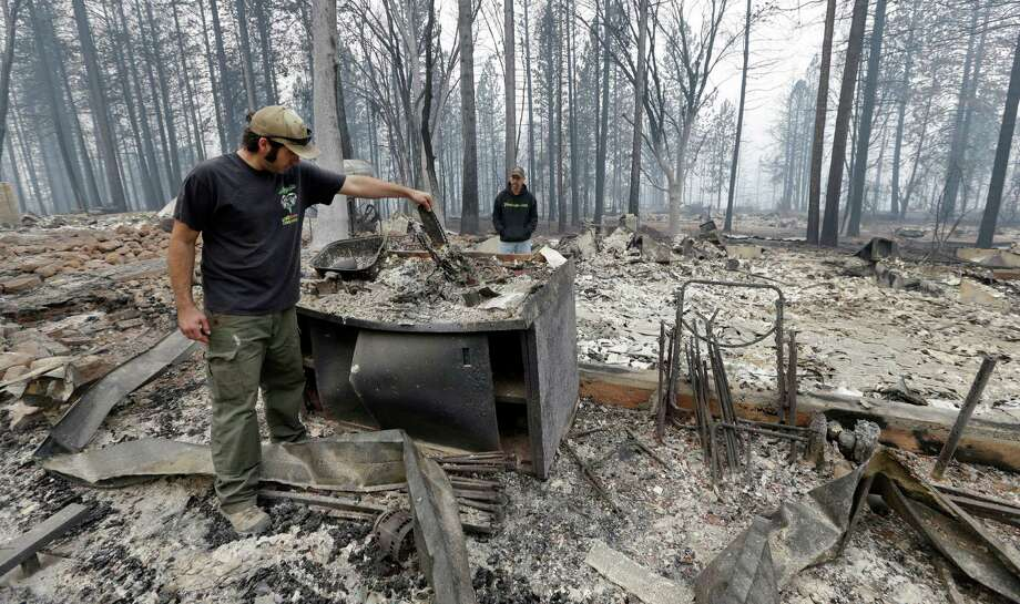 Adam Bailey, left, looks through the smoldering remains of his home Monday as his father-in-law Joel Miller looks on in Cobb, Calif. Bailey escaped the flames with his baby Saturday, just before flre roared through the neighborhood of about two dozen homes.  Photo: Elaine Thompson, STF / AP