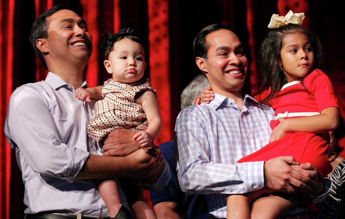 U.S. Rep. Joaquin Castro, D-San Antonio, (from left) with his daughter Andrea Elena and his twin brother HUD Secretary Julián Castro with his daughter Carina are all smiles during their 40th birthday celebration Sept. 15, 2014, at the Tobin Center for the Performing Arts.
