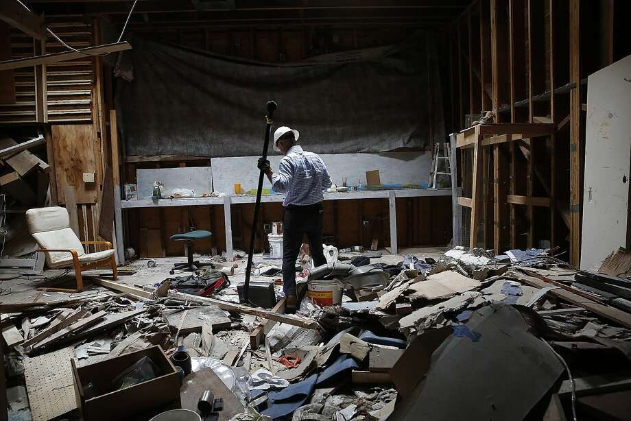 Walter Dawdiak walks through a vacant building that is often used by smash-and-grab thieves to sort their stuff. What they don't want, they just dump on the floor. Photo: Liz Hafalia, The Chronicle