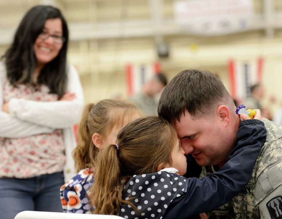 Connecticut National Guard Staff Sgt. Zakary Root, huddles with his daughters; Zoe, 6, and Jayden, 5, as his wife Monica looks-on before his unit, National Guard's 1-169 General Support Aviation Battalion departs from the guard's Aviation Support Facility in Windsor Locks, Conn., to Fort Hood, Texas, Wednesday, April 22, 2015. The 90-member unit will undergo further training and validation in Texas before begging deployed to Kosovo. (Sean D. Elliot/The Day via AP)  MANDATORY CREDIT Photo: Sean D. Elliot, MBR / THE DAY