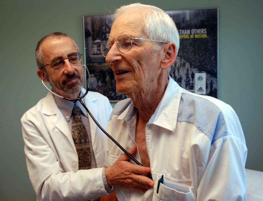 Dr. Bruce Stowell examines patient Robert Busch at his office in Grants Pass, Ore. Doctors say primary care is growing fragmented.    Photo: Jeff Barnard /Associated Press / AP