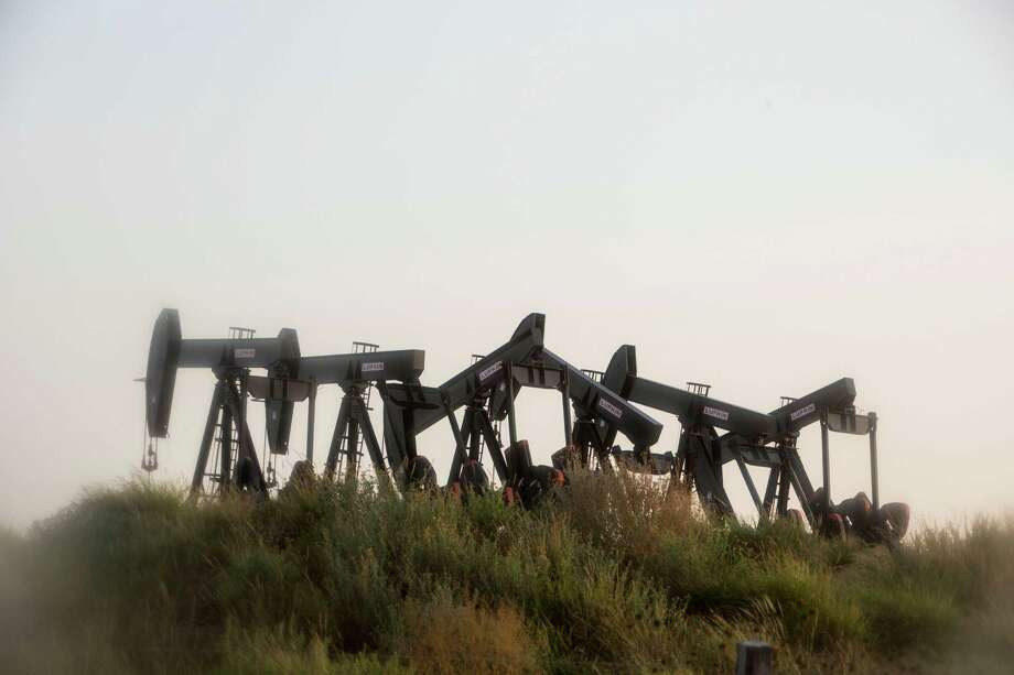 Six pumpjacks stand outside of Cotulla. Even though 73 percent of the nation's oil rigs have been sidelined since October 2014, U.S. crude production has slipped less than 5 percent from its peak in April, according to data compiled by the Federal Reserve Bank of Dallas. Photo: Carolyn Van Houten /San Antonio Express-News / San Antonio Express-News