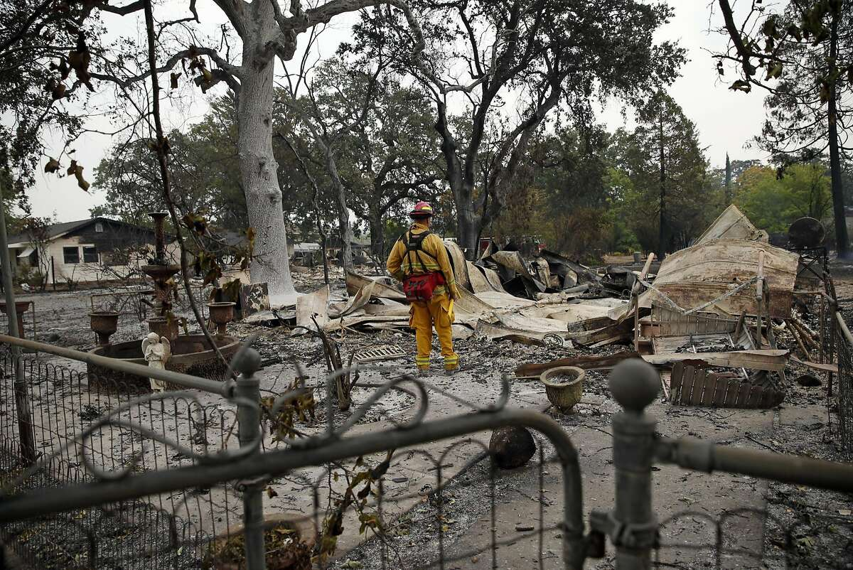 A firefighter surveys the result of the Valley Fire on Barnes Street in Middletown, Calif., on Monday, September 14, 2015.