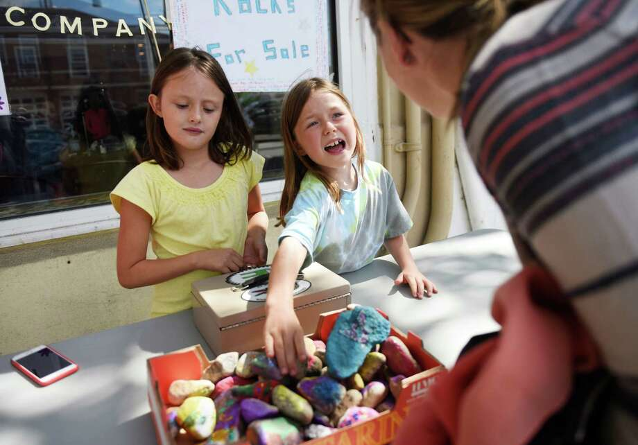 Old Greenwich 7-year-olds Clara Pita, left, and Anna Lenschow, sell painted rocks outside of Sweet Pea's Bakery in Old Greenwich, Conn. Monday, Sept. 14, 2015.  A group of Old Greenwich girls has been selling their painted rocks outside of Sweet Pea's to raise money for the Save the Children non-profit to help with Syrian refugee relocation efforts. Photo: Tyler Sizemore / Hearst Connecticut Media / Greenwich Time