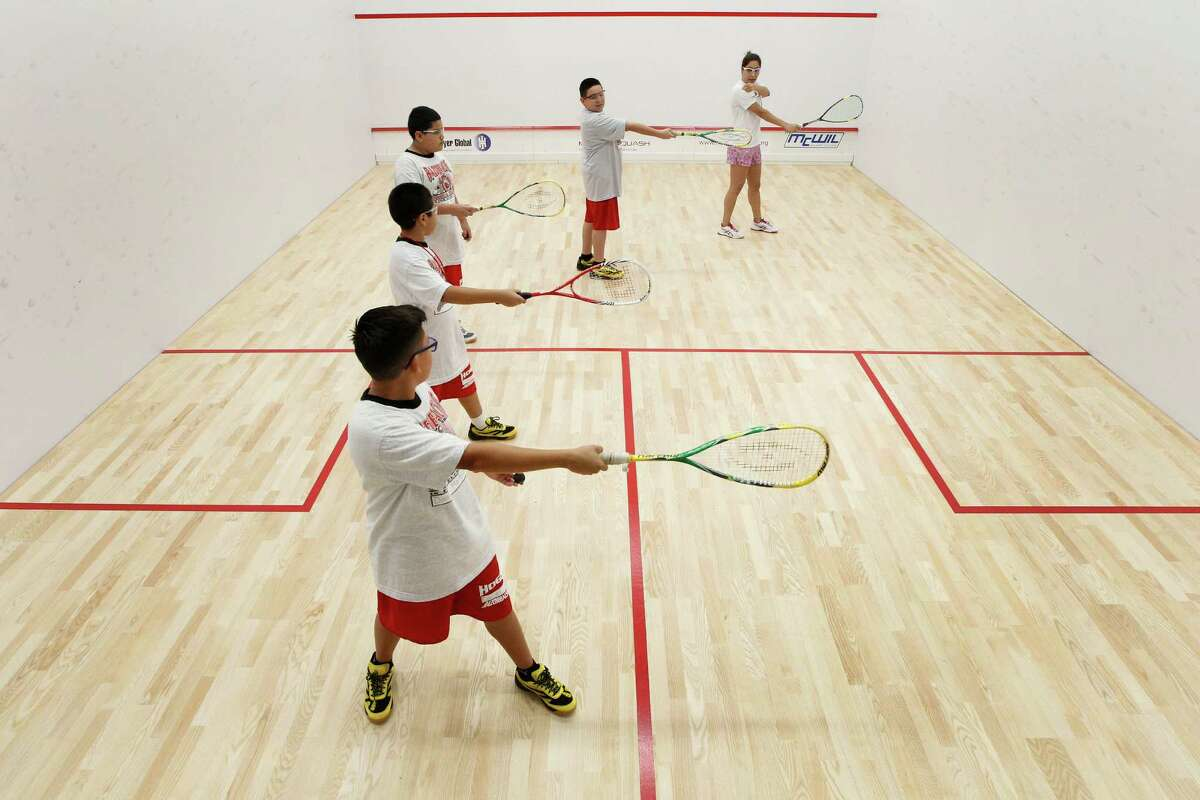 Squash Director Darya Musavi, right, leads students in their first squash lesson on Sept. 8 at Hogg Middle School.