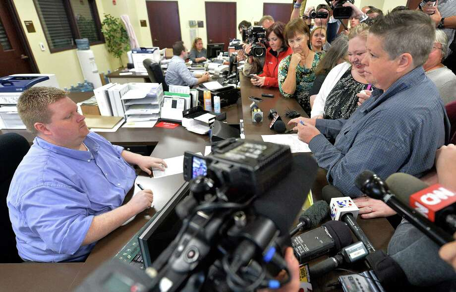 Rowan County deputy clerk Brian Mason, left, asks Shannon Wampler-Collins, right, and her partner Carmen Wampler-Collins to double check their marriage license Monday at the Rowan County Judicial Center in Morehead, Ky., as reporters and protesters stand watch. Photo: Timothy D. Easley, FRE / FR43398 AP