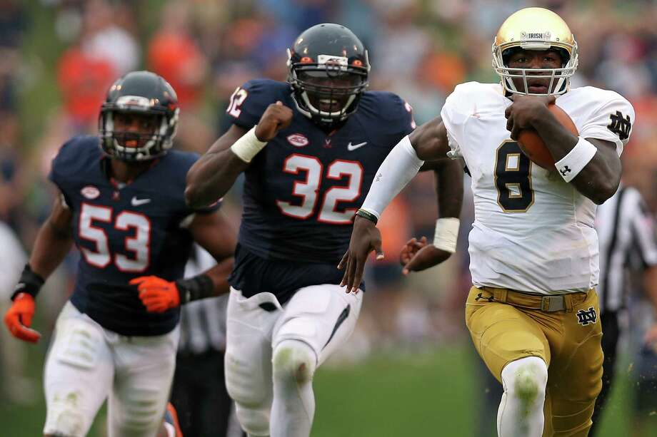 CHARLOTTESVILLE, VA - SEPTEMBER 12: Quarterback Malik Zaire #8 of the Notre Dame Fighting Irish rushes past defensive end Mike Moore #32 of the Virginia Cavaliers in the third quarter at Scott Stadium on September 12, 2015 in Charlottesville, Virginia. The Notre Dame Fighting Irish won, 34-27. (Photo by Patrick Smith/Getty Images) ORG XMIT: 567728715 Photo: Patrick Smith / 2015 Getty Images