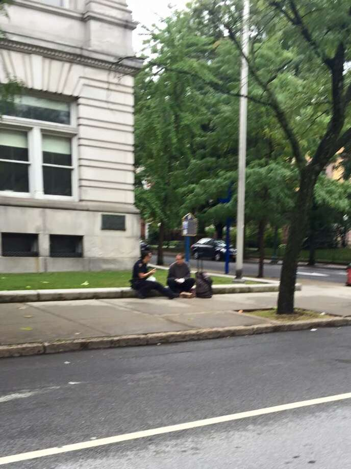 Eric Dineen, right, eats breakfast with Troy Police Officer Danielle Coonradt on the street on Sunday, Sept. 13, 2015. (Photo provided by Kyle McCauley Belokopitsky )