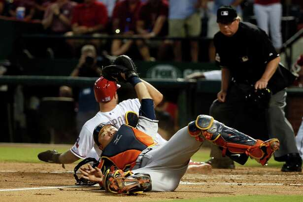 Houston Astros catcher Hank Conger holds his glove up containing the ball after tagging out Texas Rangers' Mike Napoli, left rear, as umpire Gerry Davis watches in the second inning of a baseball game Monday, Sept. 14, 2015, in Arlington, Texas. Napoli was tagged out by Conger trying to score from first on a double by Rougned Odor. (AP Photo/Tony Gutierrez)