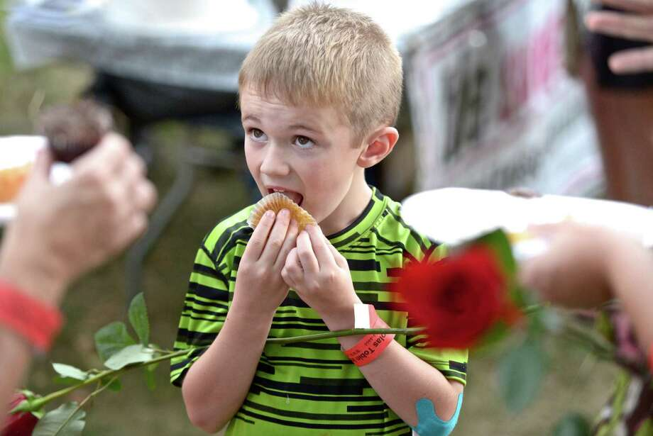 James Tong, 6, of New Milford, licks the last bit of a  cup cake off a wrapper while his mom talks with a friend at the 10th Annual Taste of New Milford, held on the Village Green, on Wednesday night, September 9, 2015, in New Milford, Conn. Photo: H John Voorhees III / Hearst Connecticut Media / The News-Times
