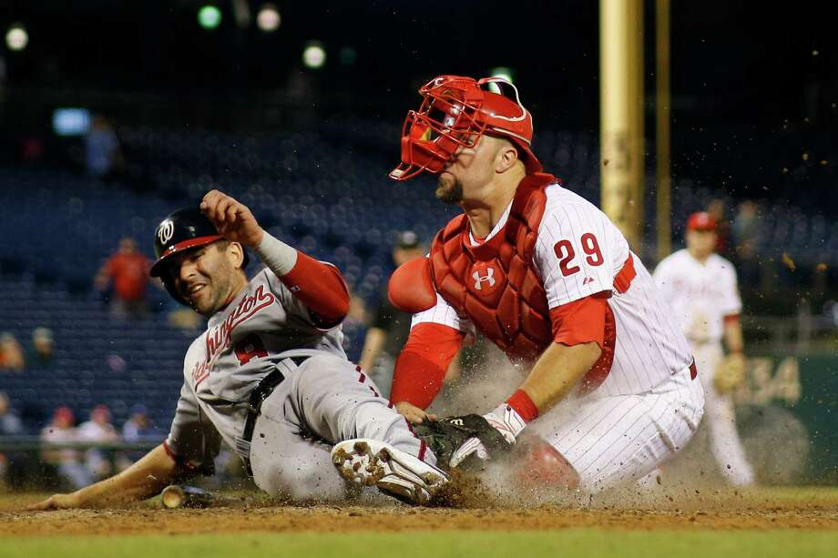 Washington Nationals' Danny Espinosa, left, slides past Philadelphia Phillies catcher Cameron Rupp to score the go-ahead run on a fielder's choice by Yunel Escobar during the 12th inning of a baseball game, Monday, Sept. 14, 2015, in Philadelphia. Escobar was safe at first. Washington won 8-7. (AP Photo/Matt Slocum) ORG XMIT: PXS110 Photo: Matt Slocum / AP