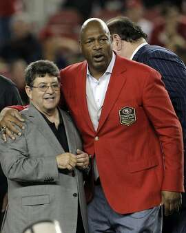 Charles Haley hugs Eddie DeBartolo after he was honored at halftime as he was inducted into the 49ers hall of fame surrounded by teammates and other Hall of Fame members, and members of the DeBartolo family during the 49ers game against the Minnesota Vikings at Levi's Stadium in Santa Clara, Calif., on Monday, September 14, 2015.