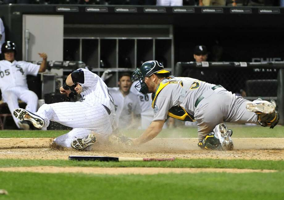 The White Sox's Geovany Soto (left) scores the winning run on a single by Melky Cabrera as A's catcher Carson Blair makes a late tag during the 14th inning of Chicago's 8-7 victory. Photo: David Banks, Getty Images