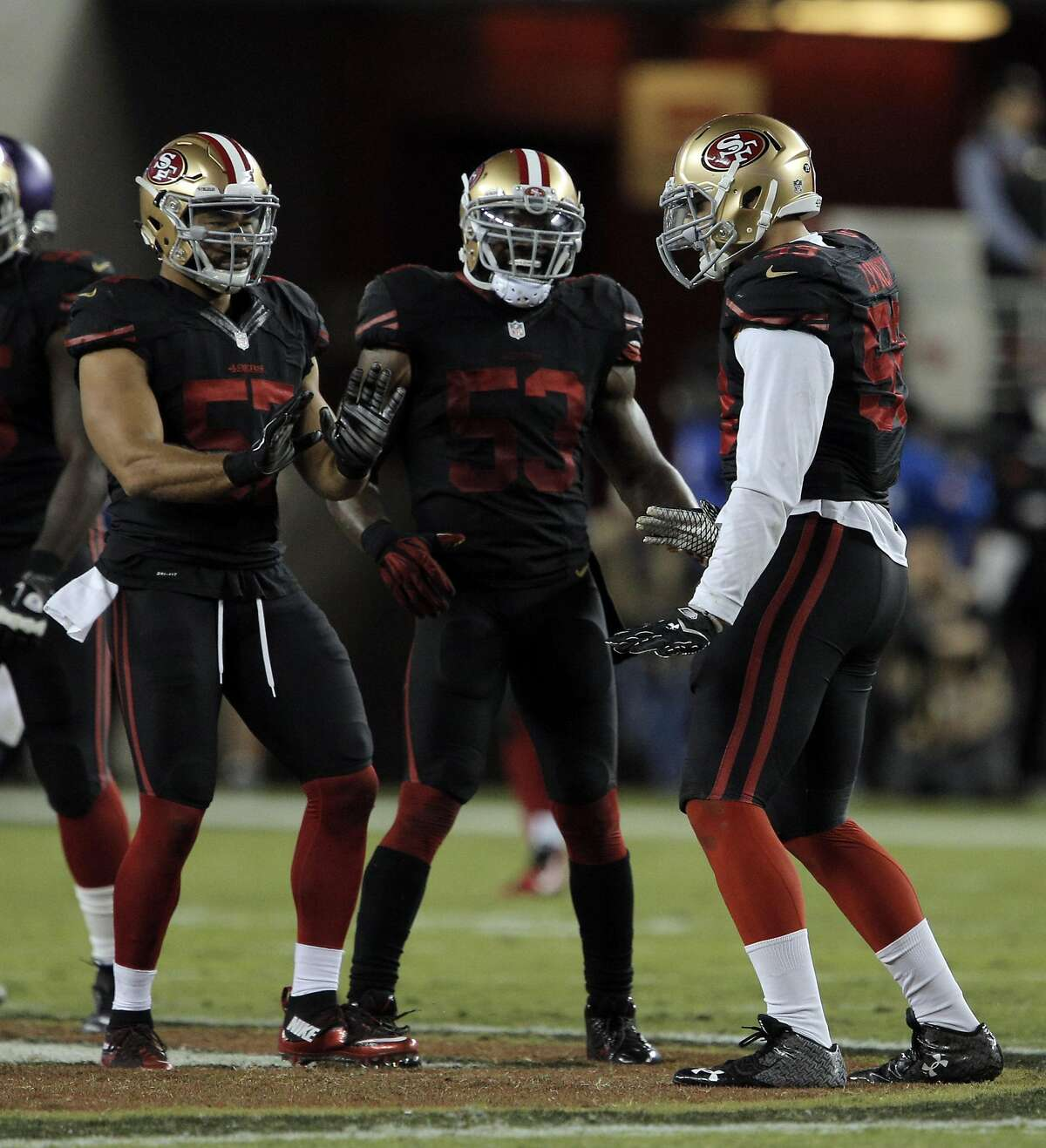 Michael Wilhoite (57), NaVorro Bowman (53) and Aaron Lynch (59) celebrate Lynch's fourth quarter sack of Teddy Bridgewater during the 49ers game against the Minnesota Vikings at Levi's Stadium in Santa Clara, Calif., on Monday, September 14, 2015.
