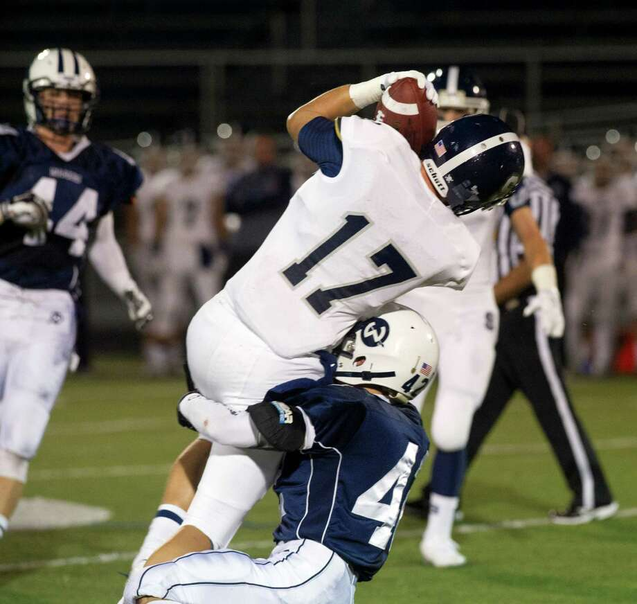 Staples' Ryan Fitton makes a catch during Friday's football game at Wilton High School on September 19, 2014. Photo: Lindsay Perry / Lindsay Perry / Stamford Advocate