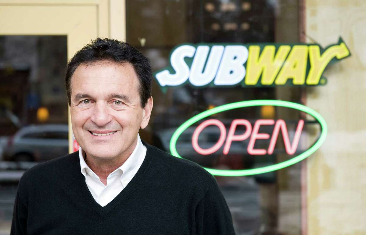 Fred DeLuca, president and co-founder of the Subway Restaurant chain, poses during an interview in front of a Subway restaurant at