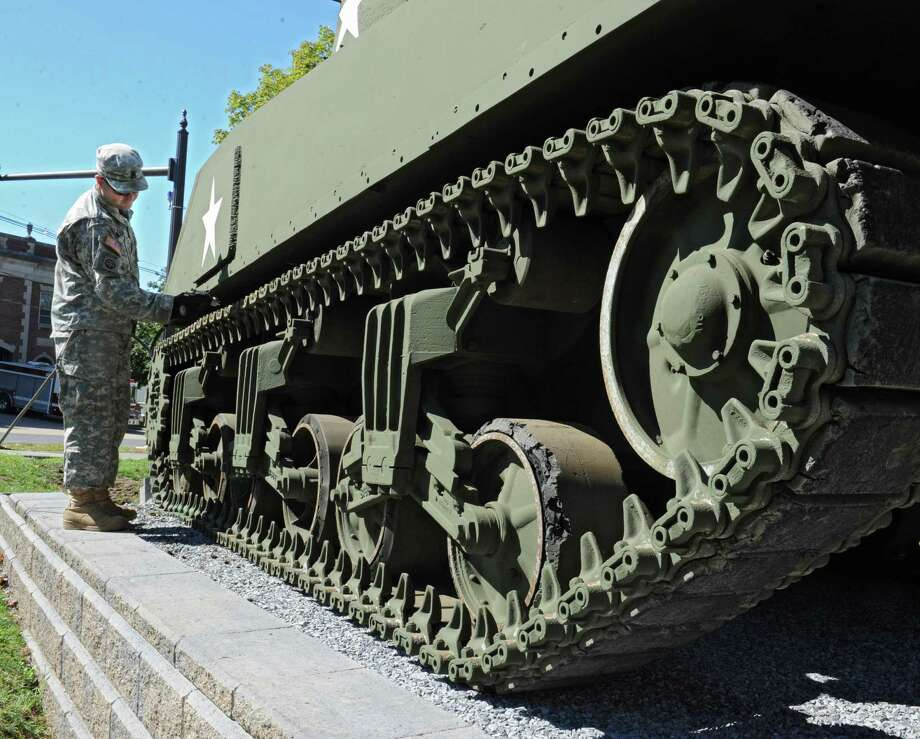 Army National Guard Staff Sgt. Cory Peck of Great Bend sprays away mud from the tracks of a World War II-era M4A3 Sherman tank that was just installed for public display at the New York State Military Museum on Tuesday, Sept. 15, 2015 in Saratoga Springs, N.Y. (Lori Van Buren / Times Union) Photo: Lori Van Buren / 00033351A