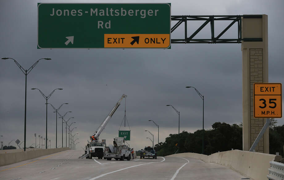 A construction crew puts an exit sign on a pole Tuesday Septeber 15, 2015 on the eastbound section of Wurzbach Parkway between West Avenue and Jones Maltsberger. That section of Wurzbach Parkway, which spans over U.S. Highway 281 North, will open Tuesday afternoon according to a TxDOT worker at the site. The westbound section is expected to remain closed until September 23. Photo: John Davenport, San Antonio Express-News / ©San Antonio Express-News/John Davenport