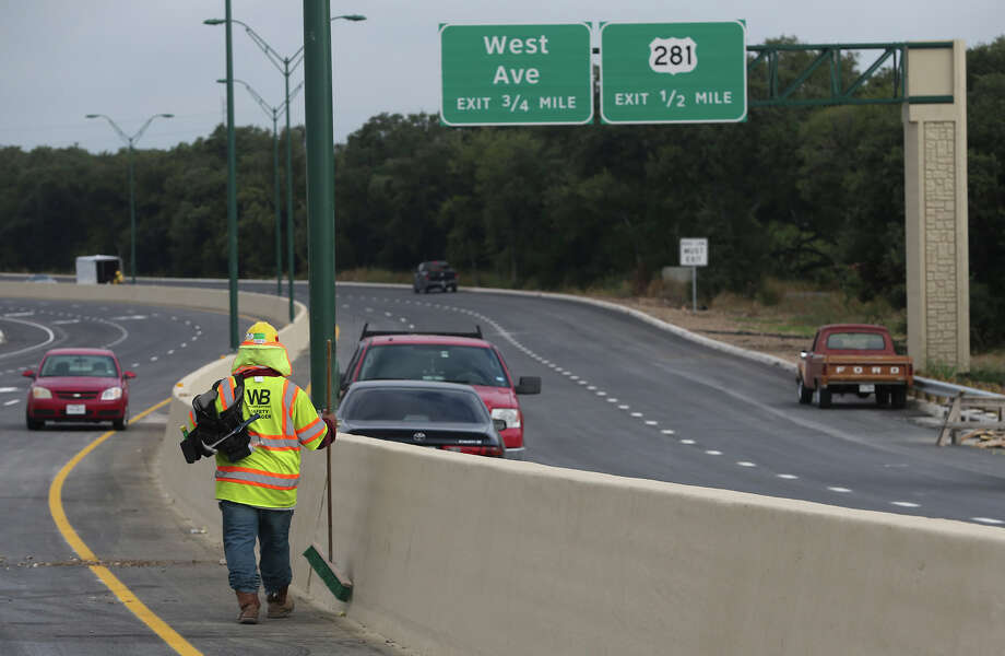 A construction worker carries a broom Tuesday Septeber 15, 2015 on the eastbound section of Wurzbach Parkway between West Avenue and Jones Maltsberger. That section of Wurzbach Parkway, which spans over U.S. Highway 281 North, will open Tuesday afternoon according to a TxDOT worker at the site. The westbound section is expected to remain closed until September 23. Photo: John Davenport, San Antonio Express-News / ©San Antonio Express-News/John Davenport
